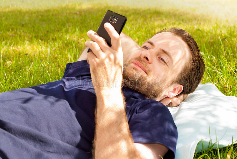 Happy man looking at mobile phone while laying on grass