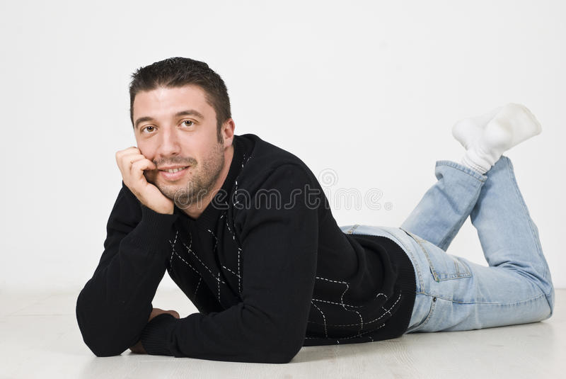 Happy man lying on wooden floor stock images