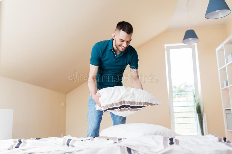Happy man making bed at home stock images