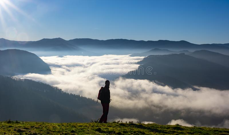 Happy Man on mountain summit enjoying aerial view over clouds. royalty free stock photo