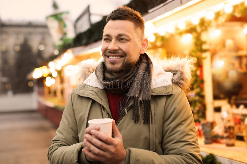 Happy man with mulled wine at winter fair stock photos