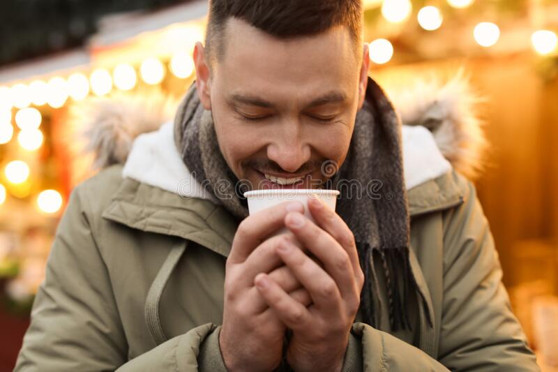 Happy man with mulled wine at winter fair royalty free stock image