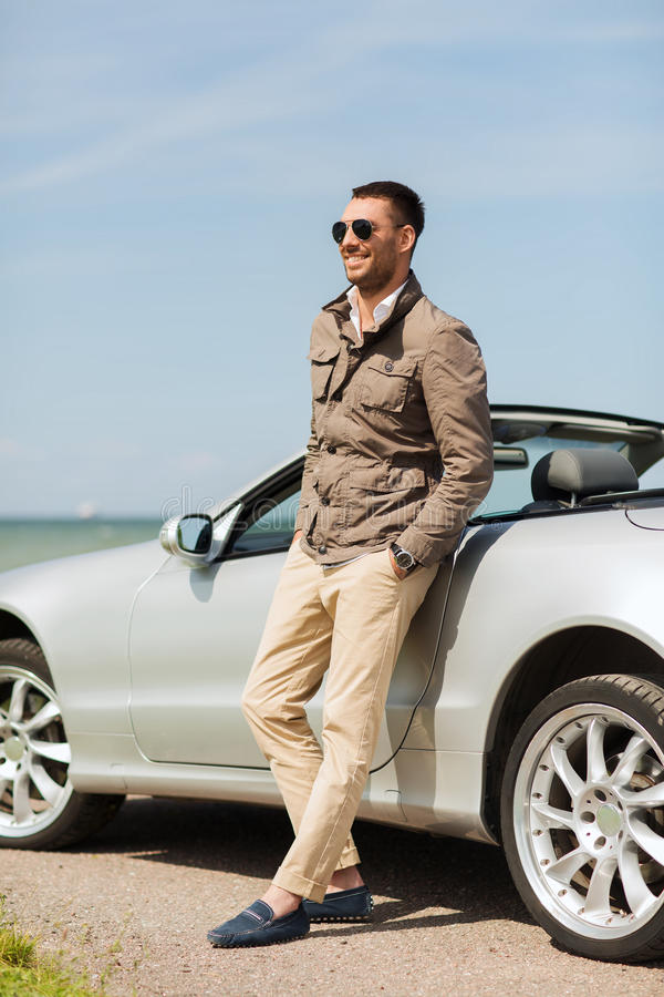 Happy man near cabriolet car outdoors. Auto business, transport, leisure and people concept - happy man near cabriolet car outdoors stock photos