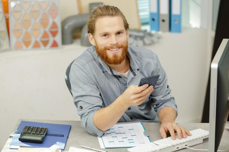 Happy man in office holding swatch royalty free stock images