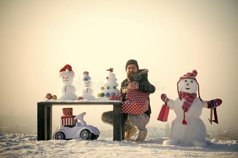 Happy man opening gift box. Snowman with shopping bags on white sky. Snowy sculptures and xmas tree on wooden table. Toy car on snow. Christmas and new year royalty free stock photography