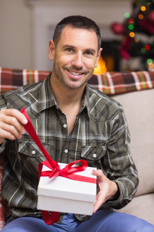 Happy man opening a gift on christmas day. At home in the living room royalty free stock images