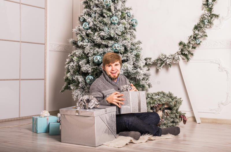 Happy man opening a gift at home near christmas tree.  royalty free stock images