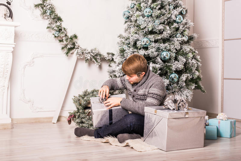 Happy man opening a gift at home near christmas tree.  stock image