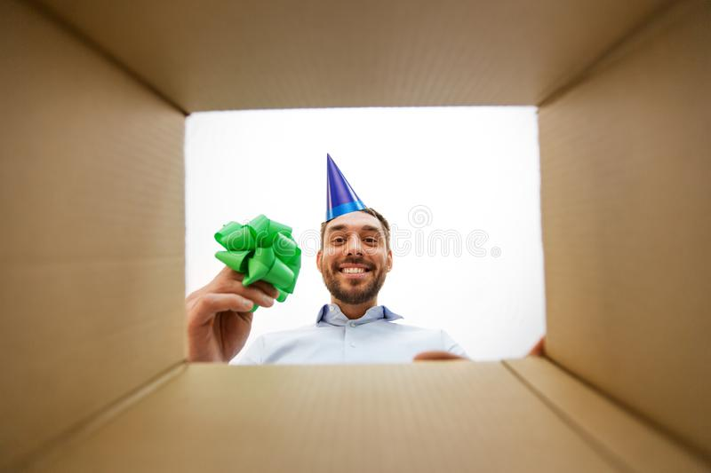 Happy man opening parcel box or birthday gift. Presents, delivery and surprise concept - happy man in party hat opening parcel box or birthday gift, from below royalty free stock photography