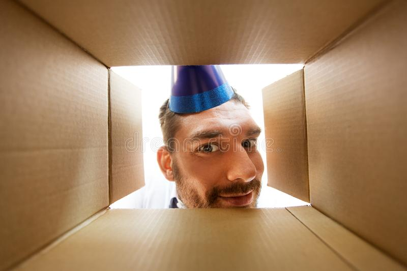 Happy man opening parcel box or birthday gift. Presents, delivery and surprise concept - happy man in party hat looking into open parcel box or birthday gift stock images