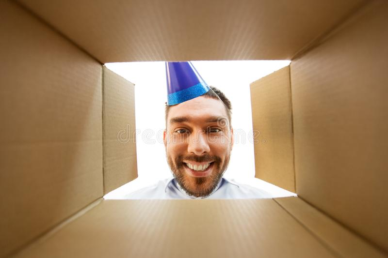 Happy man opening parcel box or birthday gift. Presents, delivery and surprise concept - happy man in party hat looking into open parcel box or birthday gift stock photos