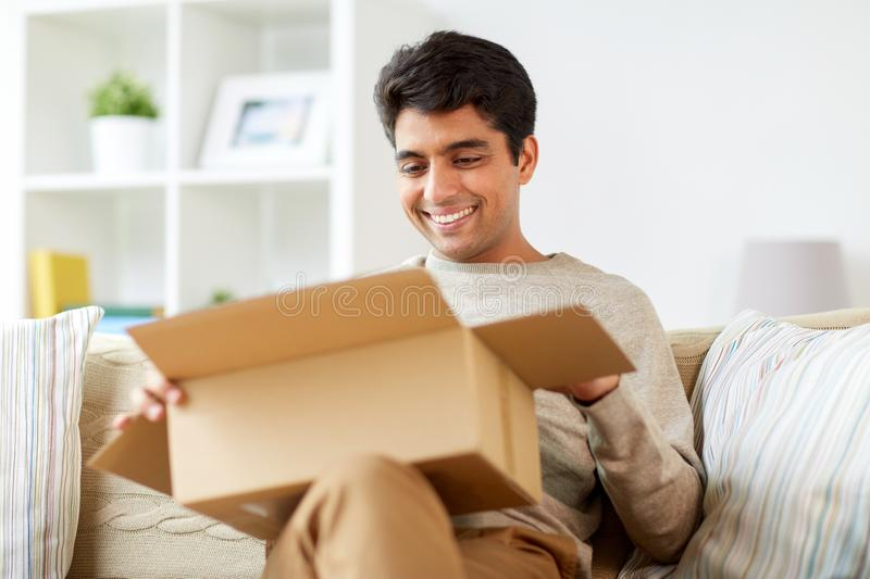 Happy man opening parcel box at home. Mail delivery, shipment and people concept - happy man opening parcel box at home royalty free stock photography