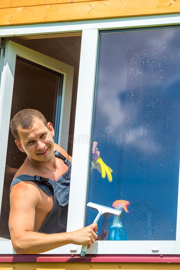 Happy man in overalls washes a window royalty free stock photo