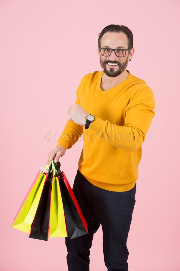 Bearded man has time for shopping. Smiling guy in glasses has time for new purchases. Happy man with paper bags showing time. royalty free stock images