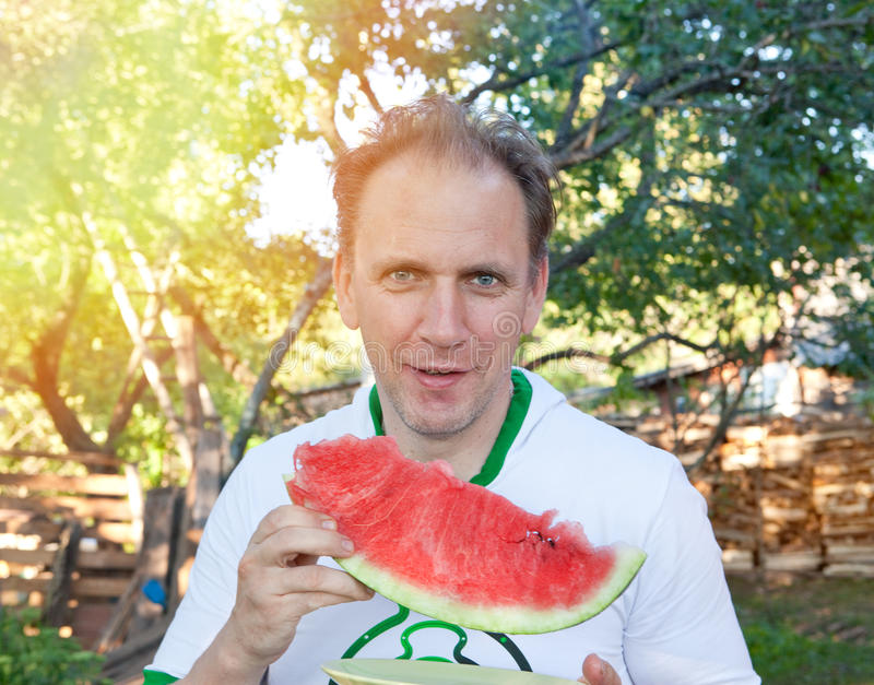 happy man with a piece of a water-melon royalty free stock image