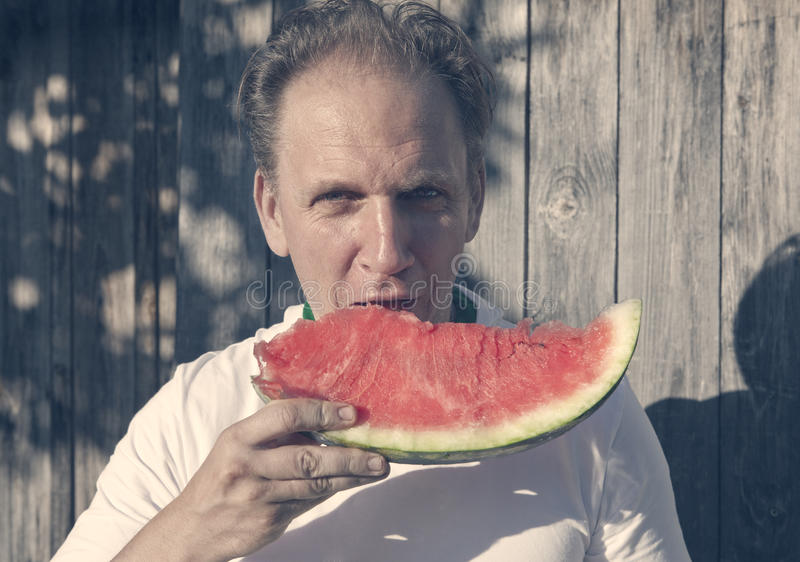 Happy man with a piece of a water-melon, with a vintage effect stock photography