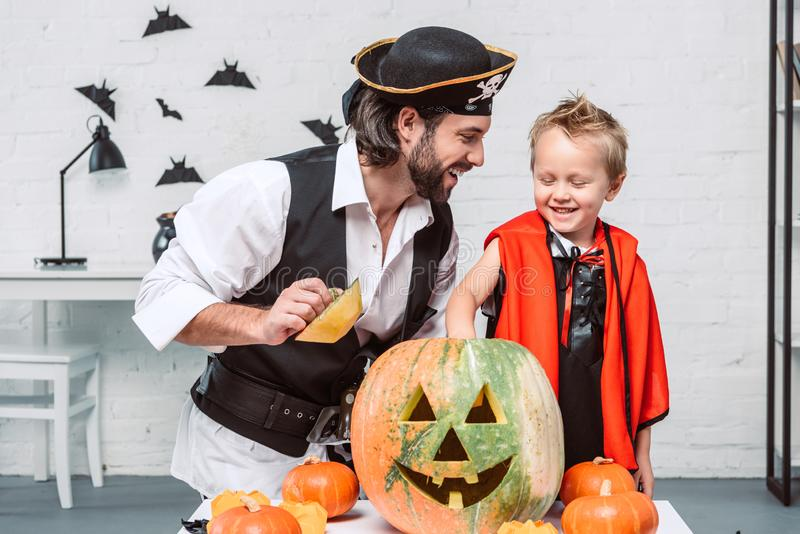 Happy man in pirate costume and son in vampire halloween costume with pumpkin together. Happy men in pirate costume and son in vampire halloween costume with stock images