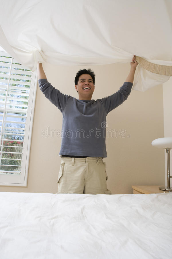 Happy Man Preparing Bed At Home stock photo