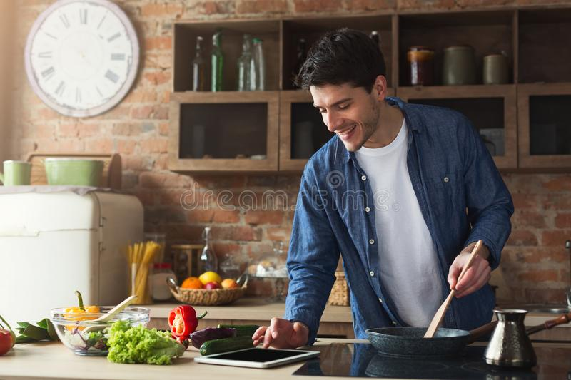 Happy man preparing healthy food in the home kitchen. Happy man cooking healthy food with recipe, looking on digital tablet in the loft kitchen at home on sunny royalty free stock photography