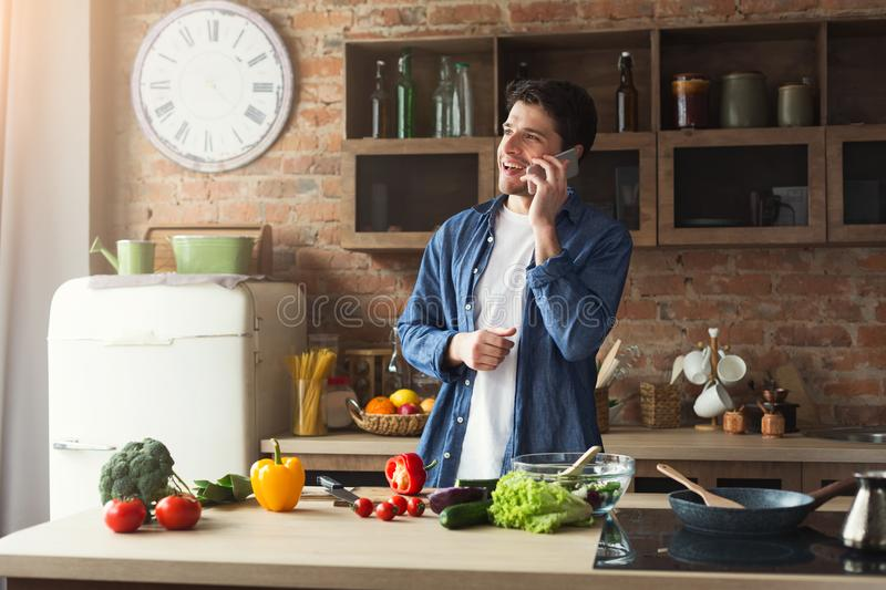 Happy man preparing healthy food in the home kitchen. Happy man cooking healthy food and talking on smartphone in the loft kitchen at home on sunny day royalty free stock photo