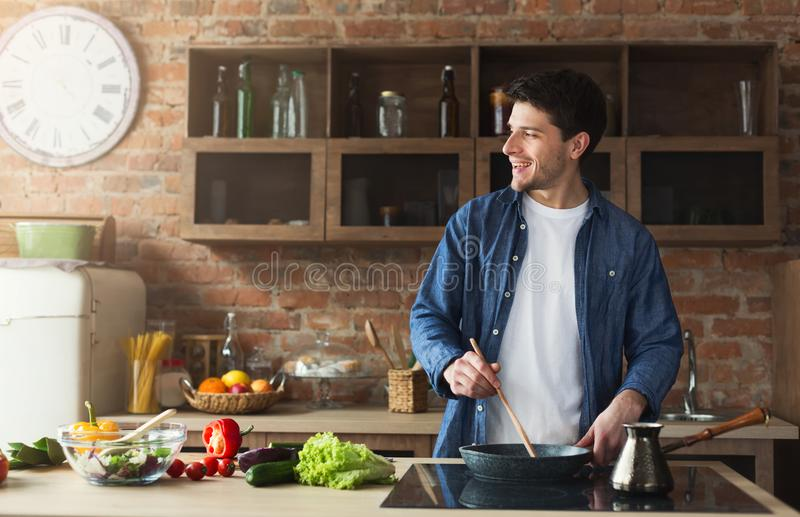 Happy man preparing healthy food in the home kitchen. Happy man cooking delicious and healthy food in the loft kitchen at home on sunny day. Preparing vegetable royalty free stock image