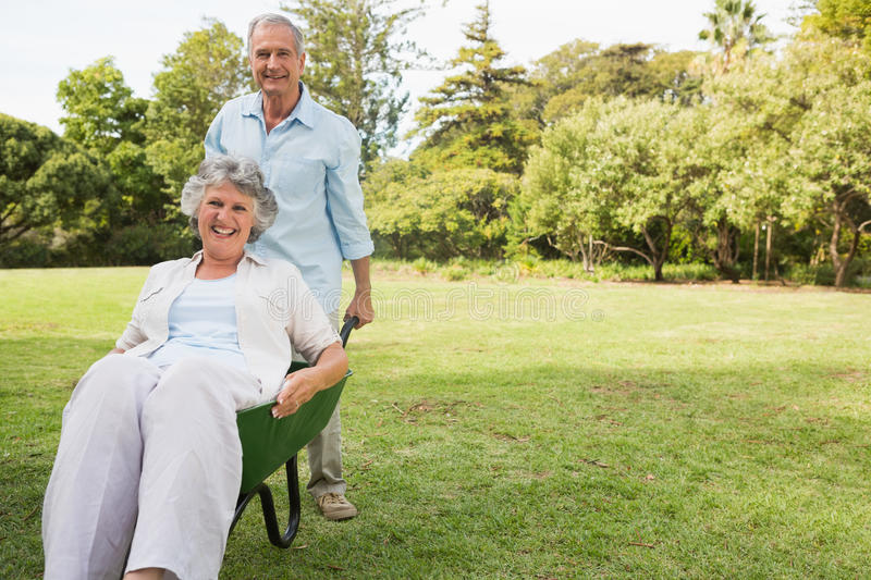 Happy man pushing his wife in a wheelbarrow royalty free stock images