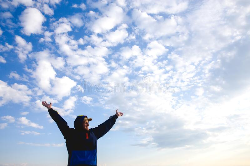 Happy man raised wide open arms traveling hiker blue sky and clouds healthy lifestyle adventure vacations outdoor success joyful stock images