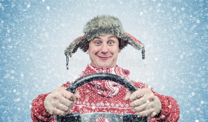 Happy man in red sweater and hat with a steering wheel, snow blizzard. Concept car driver stock photography