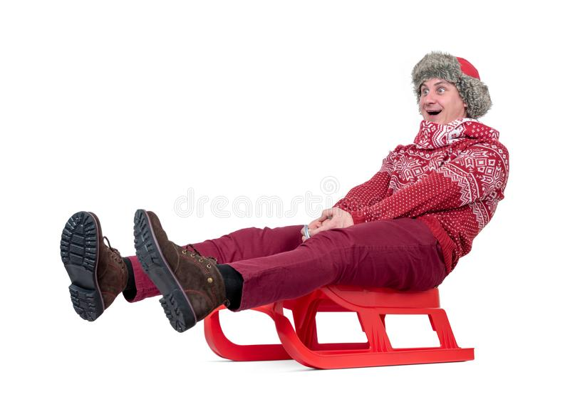 Happy man in a red sweater, scarf and hat rides a sled, isolated on white background stock photography
