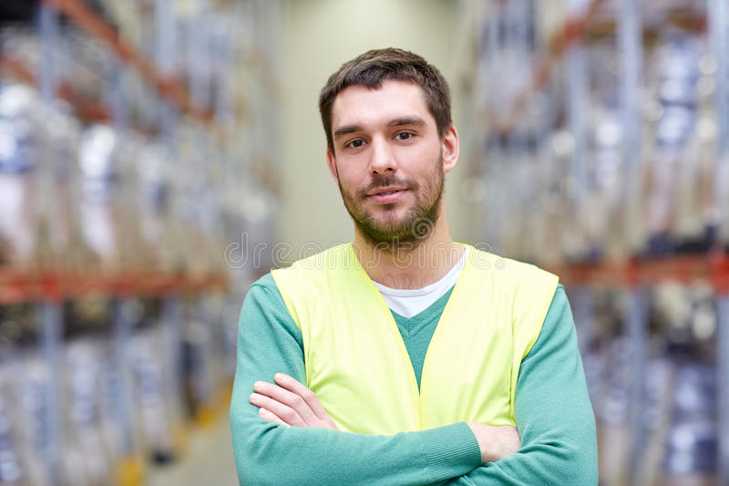 Happy man in reflective safety vest at warehouse. Wholesale, logistic, people and export concept - happy man in reflective safety vest at warehouse stock image
