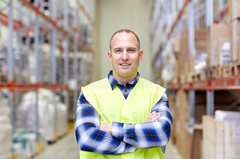 Happy man in reflective safety vest at warehouse stock photos
