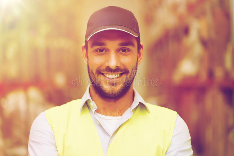 Happy man in reflective safety vest at warehouse. Wholesale, logistic, people and export concept - happy man in cap and reflective safety vest at warehouse stock photography