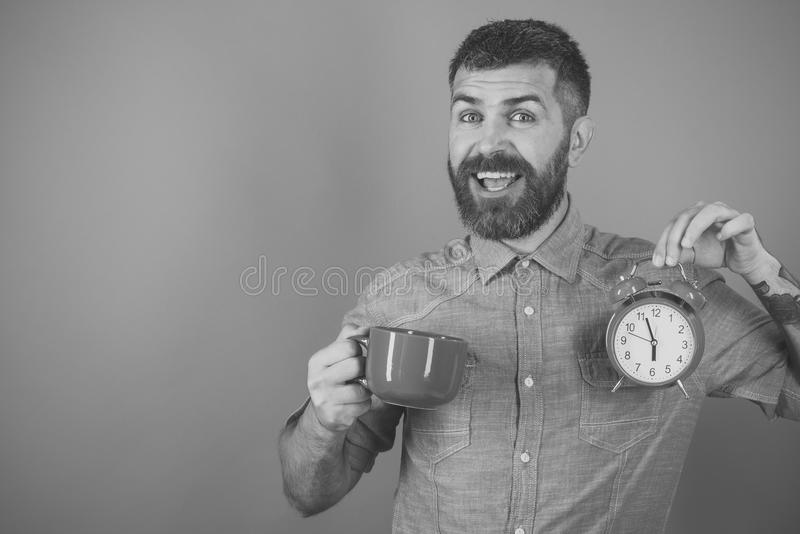 Happy man. Refreshment break and energy, copy space. Happy man. Refreshment break and energy. Happy guy with mulled wine, clock on blue background. Red mug with royalty free stock photography