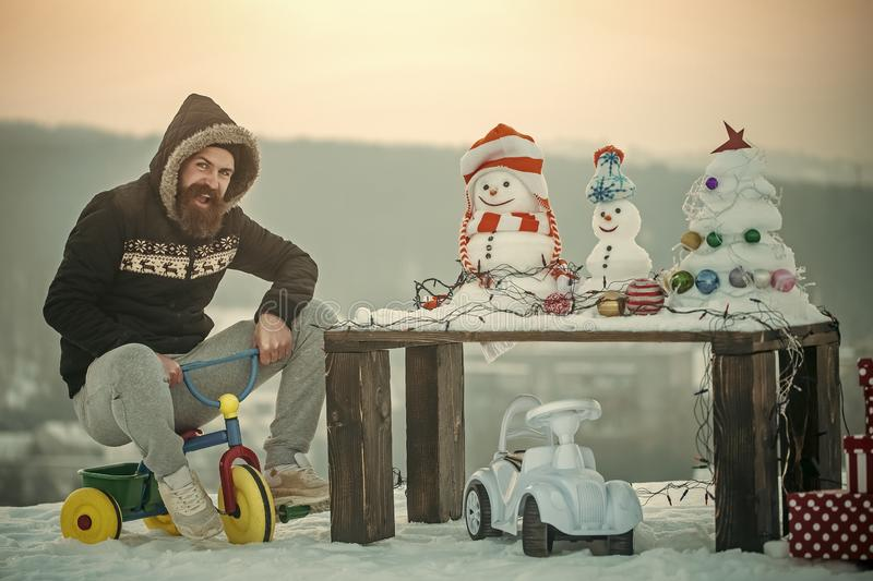 Happy man riding tricycle on snow. Snowmen, snowy xmas tree, decorations and lights on wooden table. Present boxes and toy car. Christmas and new year. Winter royalty free stock images