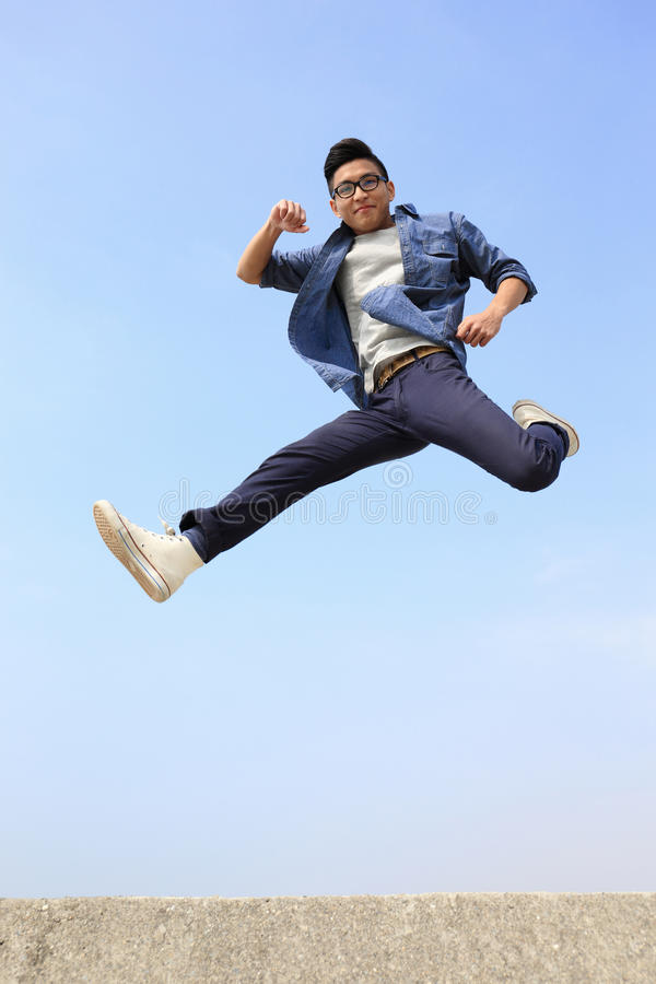 Happy man run and jump. Happy College student man run and jump with blue sky background, full length, asian male stock photo