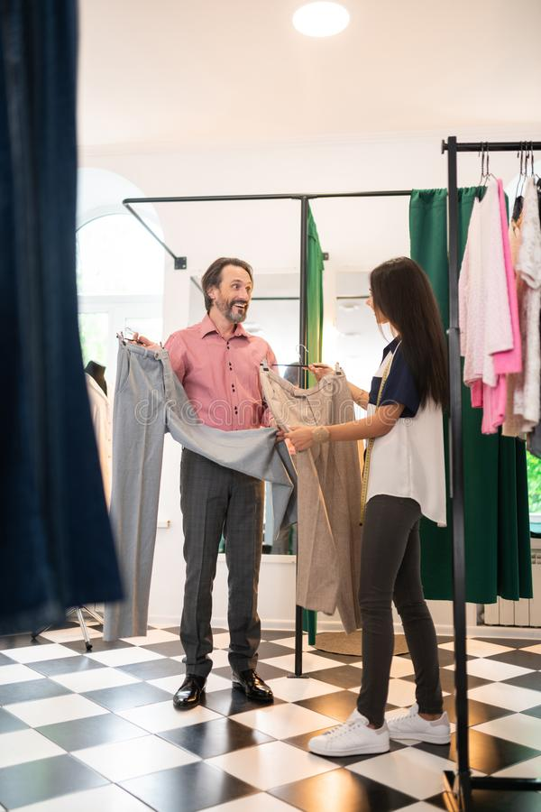 Happy man of 30s choosing a new pair of pants royalty free stock photo