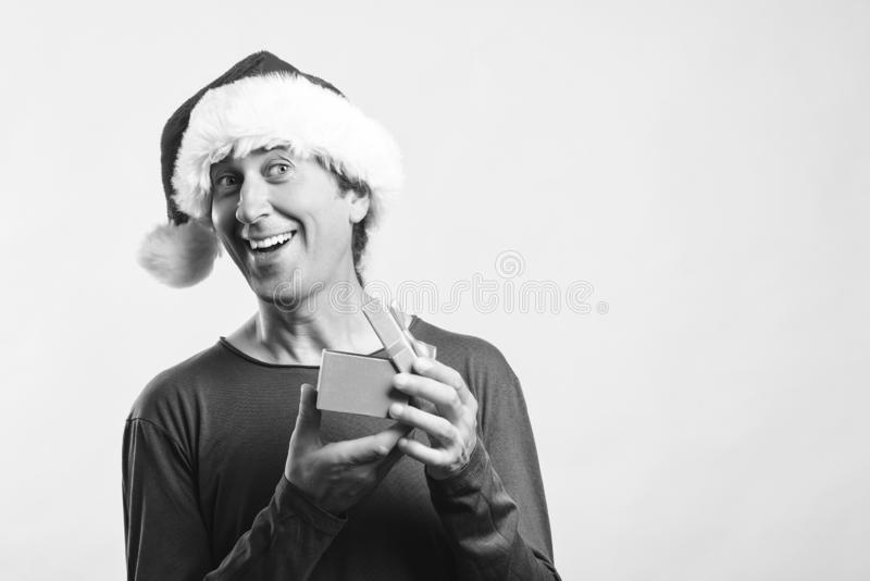 Happy man in santa hat opening a gift. Santa christmas man isolated on white, copy space. Christmas holidays. Happy man enjoying. Christmas time. Christmas royalty free stock images