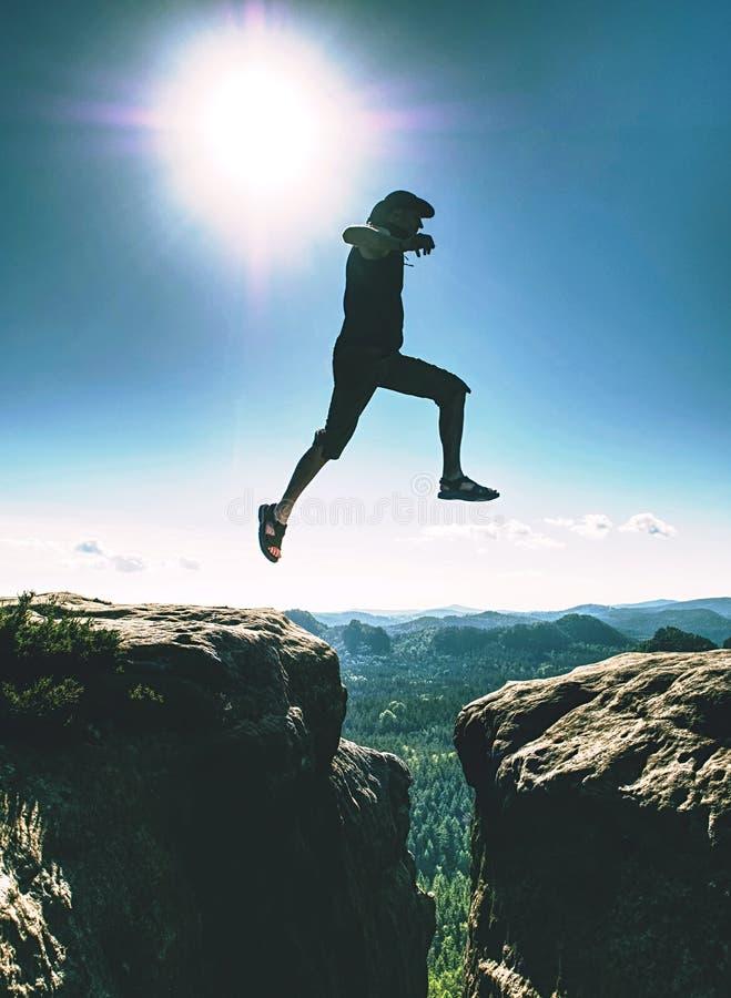 Happy Man sautant au-dessus de la falaise de grès fissurée Style de voyage images stock
