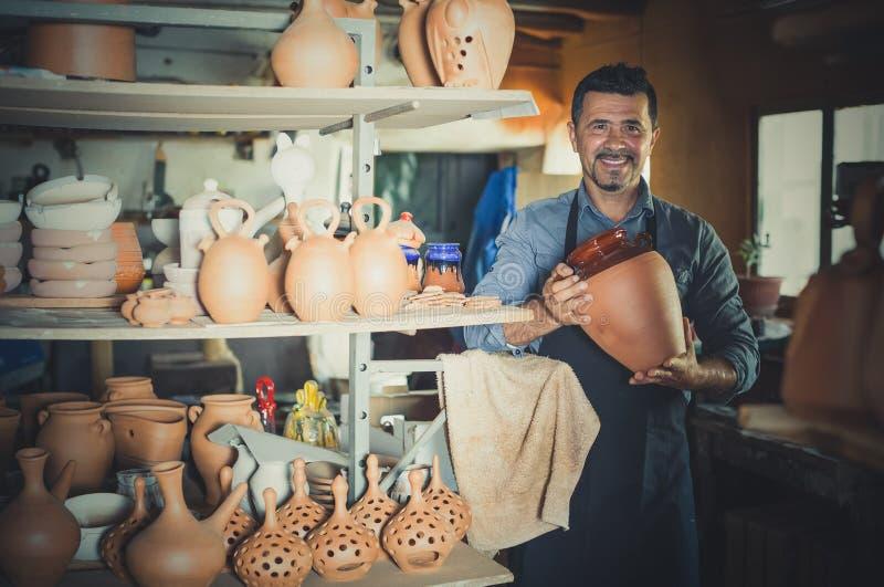 Happy man sculptor having ceramics. In hands and standing in workroom stock image