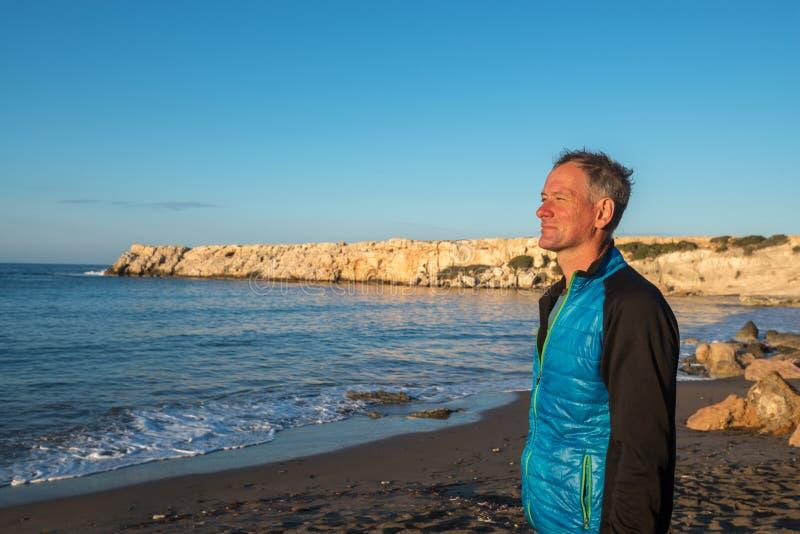 Happy man on the seashore, enjoying life during sunrise. Sunny morning on the Cape Akamas, Cyprus royalty free stock images