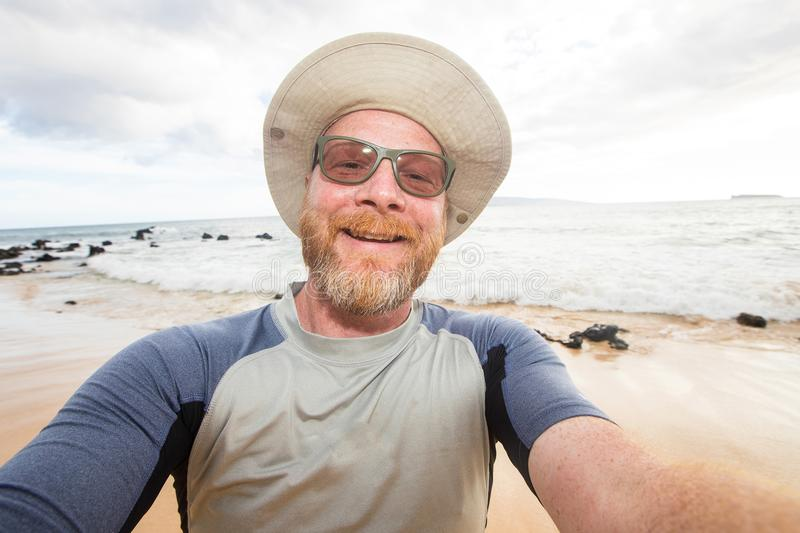 Happy man selfie at the beach. Man with beard and floppy hat at tropical beach stock image