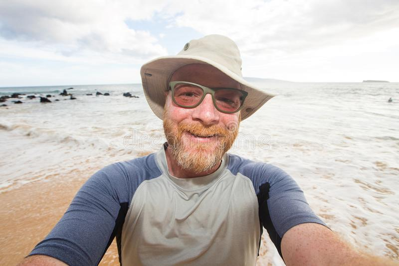 Happy man selfie at the beach. Man wearing floppy hat and sunglasses at a tropical beach stock photos