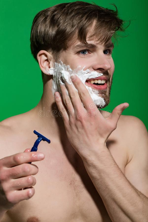 Happy man shave beard with razor on green background royalty free stock image