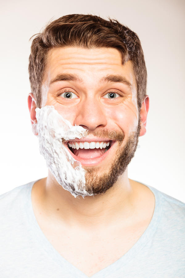 Happy man with shaving cream foam on half of face. Happy young man with shaving cream foam on half of face beard. Handsome guy preparing to shave. Skin care and royalty free stock photos