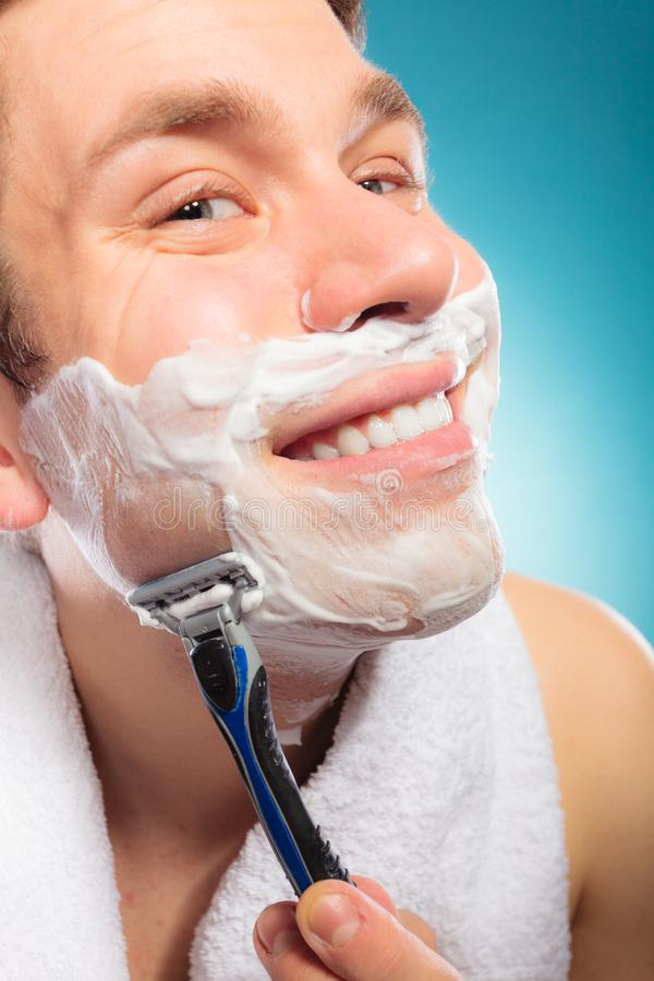 Happy man shaving using razor with cream foam. Happy smiling man shaving using razor with cream foam. Handsome guy removing face beard hair. Skin care and stock photo