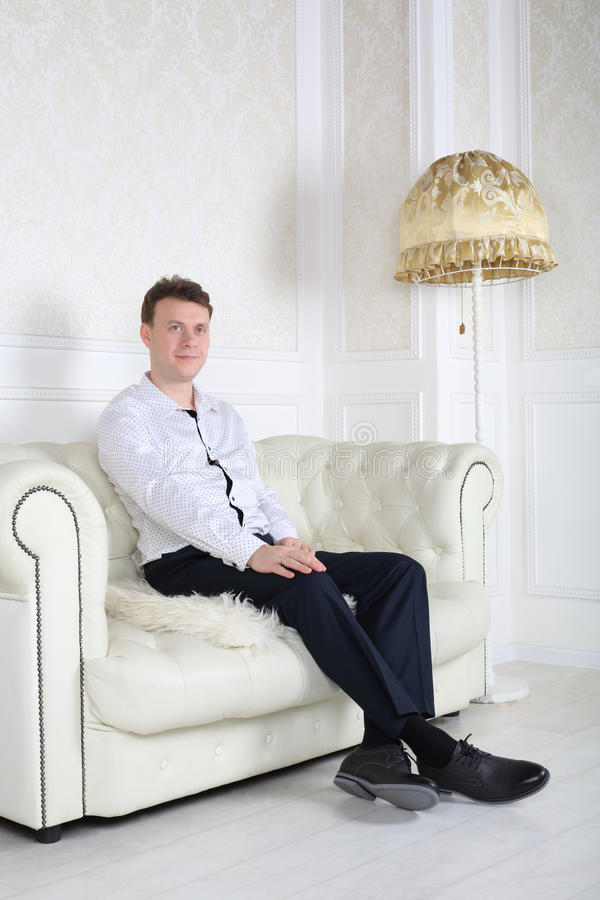 happy man in shirt sits on sofa and dreams stock photo. Black Bedroom Furniture Sets. Home Design Ideas