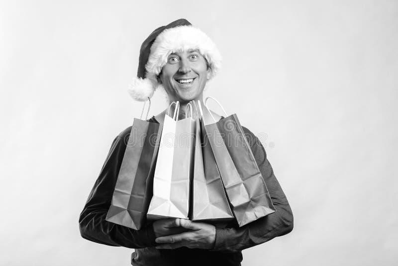 Happy man shopping christmas gifts. Christmas shopping idea concept. Man in Santa hat. Shopping bags. Santa holding shopping bags stock photography
