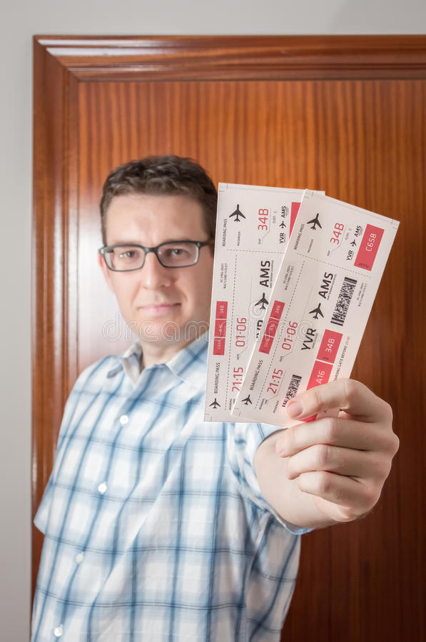 Happy man showing boarding pass ready to travel stock photography