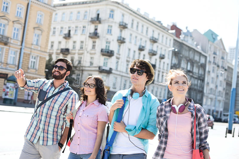 Happy man showing something to male and female friends on city street stock photo