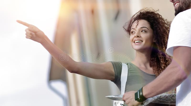 Happy man showing something to woman outside building stock photography
